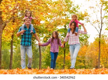 mom dad and little girls walk in forest together