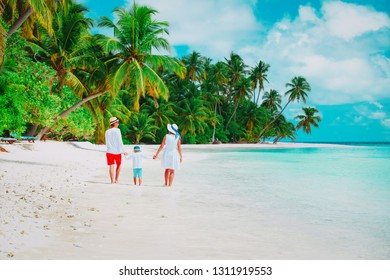 mom, dad and little son walking on beach, family on tropical vacation