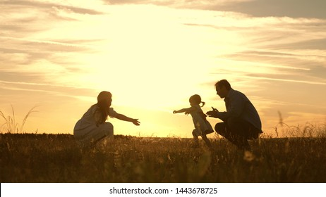 Mom and Dad playing with their daughter in park at sunset. kid takes the first steps. Happy family playing with the child in rays of sun. baby goes from dad to mom and laughs. Slow motion.