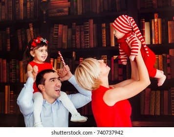 Mom and dad pose with their charming little daughter and a son before green Christmas tree