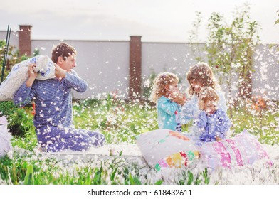 Mom, Dad, son and daughter are fighting with pillows in the yard of their house. They laugh with laughter, and feathers fly around