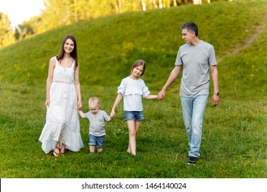 Mom, dad, son and daughter walk in the park at the weekend holding hands. Happy family in nature. fun big family in the forest.