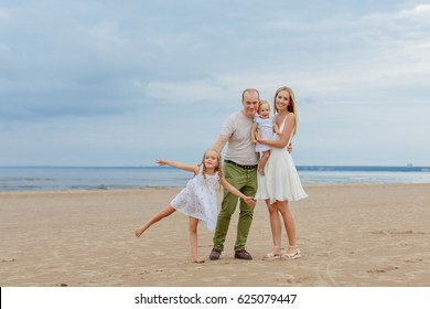 Mom, Dad and two lovely daughters go along the seashore in the summer and laugh