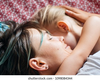 Mom and daughter in bed, the morning the baby wakes up and hugs mother. The concept of a happy family life