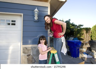 Mom and daughter being silly with paint on their faces. The mother is standing on a ladder. Horizontally framed photograph