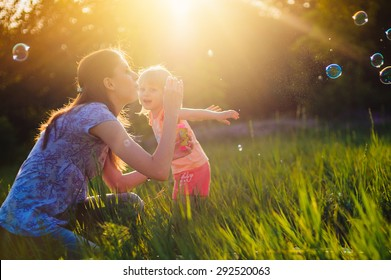 Mom and daughter blow bubbles on sunset