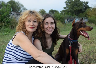 Mom with daughter and brown Doberman on walks