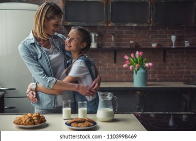 Mom and daughter in casual clothes are looking at each other and smiling while hugging in kitchen at home; cookies and milk on the table