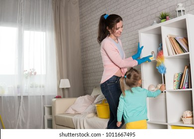 Mom and daughter are cleaning in the apartment, a woman and a girl of three years doing household chores