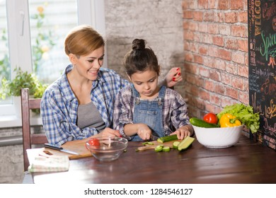 Mom and daughter cook together at home, woman and girl prepare salad in the kitchen