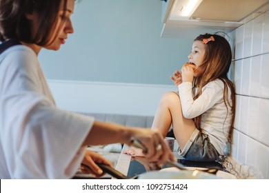 Mom and daughter cook together in the kitchen