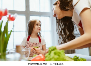 Mom and daughter cook together, look at each other and smile, mother's day