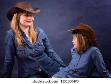 Mom and daughter in cowboy hats. Cowboy style.