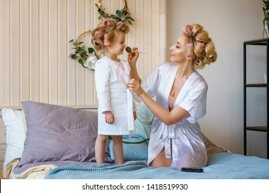 mom and daughter in curlers , make a make-up to each other, a happy family.