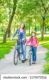 Mom and daughter are cycling in the park together