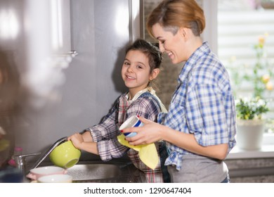 Mom and daughter do the dishes, woman and girl do the cleaning in the kitchen