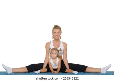 Mom and daughter do gymnastics on blue mat