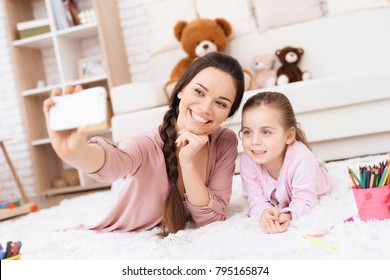 Mom and daughter do selfie on a smartphone. A young woman and a girl are lying on the floor in their apartment.