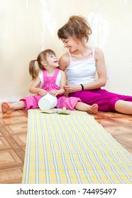 Mom and daughter are doing repairs together, wallpaper on the floor
