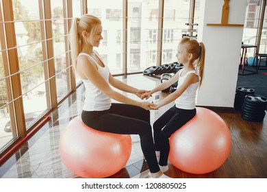 Mom and Daughter are doing yoga. Family in a gym. Little girl with mother in a white t-shirts and black leggings. Girls with red fitball