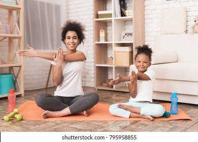 Mom and daughter are doing yoga at home. They are sitting on a rug, next to them are dumbbells. African American girl and a woman.