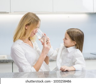 Mom and daughter drink water in the kitchen