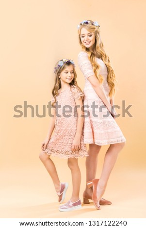 8b22c82396 mom and daughter in elegant lacy dresses and floral wreaths standing back  to back and posing at camera on yellow background - Image