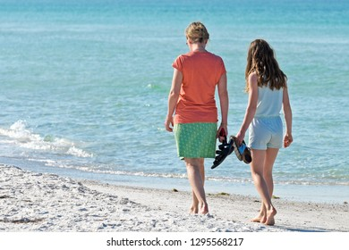 Mom and Daughter Enjoying an Early Morning Walk on the Beach in Florida