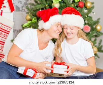 Mom and daughter exchanging Christmas gifts at home, with decorated Christmas Tree at background.