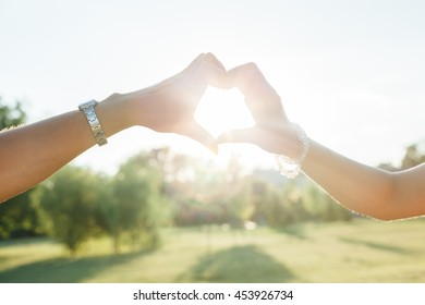 Mom and daughter forming a heart with their hands while the sun is setting