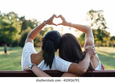 Mom and daughter forming a heart with their hands while embracing on a park bench