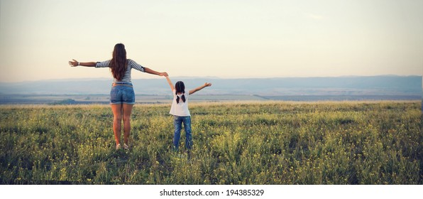 Mom and daughter go off into the distance on a beautiful meadow