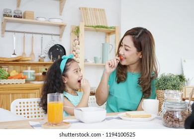 mom and daughter have breakfast in the morning