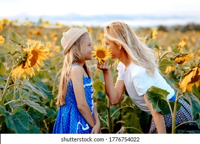 Mom and daughter are hiding behind a flower of a sunflower