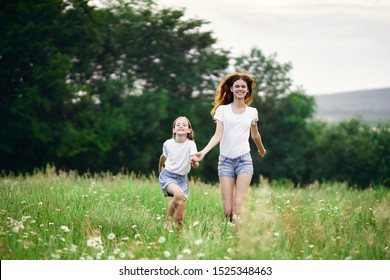 Mom and daughter hold hands walk childhood landscape of happiness