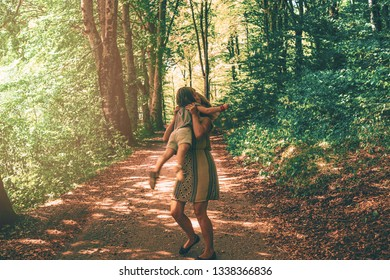 mom and daughter hug and play together in the woods. family relation and  harmony in nature concept