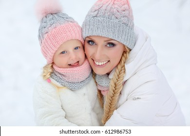 Mom and daughter hugging happy winter in the park, close-up