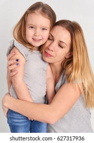Mom and daughter in jeans on a gray background