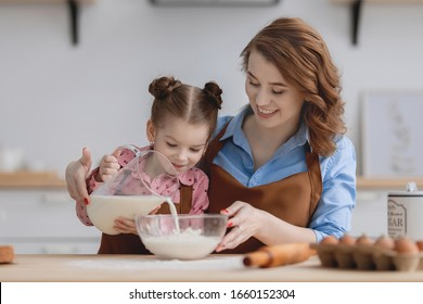 mom and daughter in the kitchen have fun and cook food from flour, milk and eggs