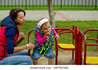 mom and daughter laugh at the children's swing child twisted on the carousel toshnit girl on the carousel