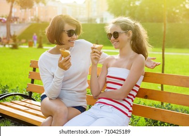 Mom and daughter laugh, eat ice cream and enjoy socializing.