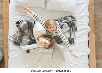 Mom and daughter lie in a white bed at home