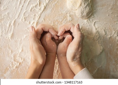 Mom and daughter make a heart with their hands while preparing the dough. Top view