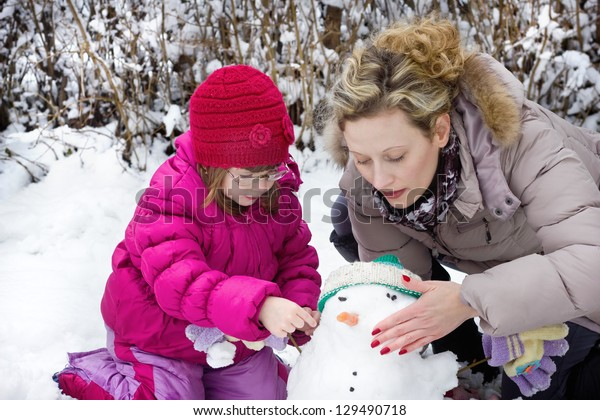 mom and daughter make a Snowman, best fokus on the mother