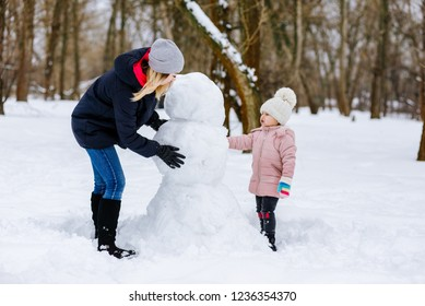 mom and daughter make a snowman out of snow