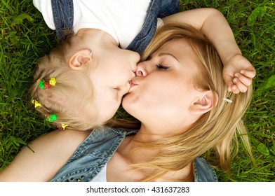 Mom and daughter in nature. gentle kiss. top view