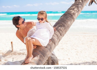 Mom and daughter on a palm tree enjoying vacations on the beach