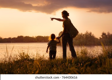 Mom and daughter on the river bank at sunset , Silhouettes a family in the evening in the summer at sunset.