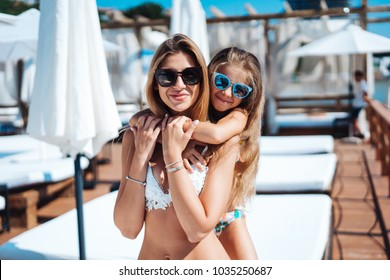 Mom and daughter on vacation posing on cameran