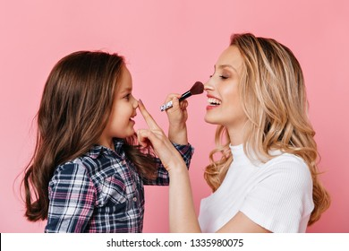 Mom and daughter play and do makeup on pink background. Snapshot of female child with makeup brush and blonde girls in white t-shirt